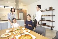 食事を置いたテーブルで笑い合う家族