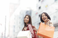 歩きながら微笑むショッピング中の女性二人
