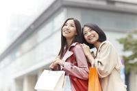 立ち止まって上を向く買い物中の女性二人