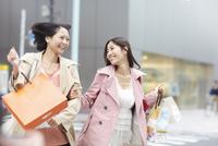 買い物中に手を組んで駆ける女性二人