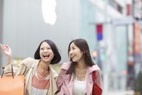買い物中に指差す方向を見て笑う女性二人