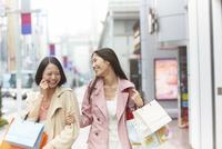 買い物中に腕を組んで笑い合う女性二人