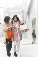 買い物中に笑い合う女性二人
