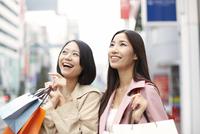 買い物中に上を見て微笑む女性二人