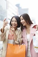 買い物中にスマートホンを見て笑う女性二人