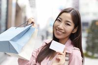 買い物バッグとカードを見せて微笑む女性