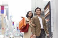 買い物中に笑いながら歩くカップル