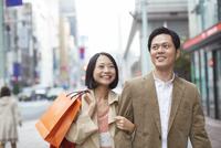 買い物中に腕を組んで歩くカップル