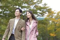 公園で腕組みして歩くカップル
