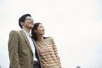 遠くを見て微笑むカップル