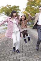 遊歩道で女の子を高く上げて笑い合う家族