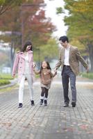 遊歩道で両親と手をつないで喜ぶ女の子