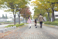 遊歩道を手をつないで歩く家族