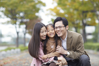 遊歩道でかがみながら微笑む家族のスナップ 33000000204| 写真素材・ストックフォト・画像・イラスト素材|アマナイメージズ