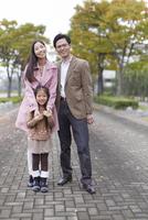 遊歩道で立って微笑む家族のスナップ