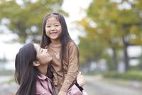 遊歩道で母に抱かれて微笑む女の子