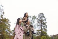 木をバックに肩車して遠くを見る家族