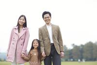 公園で手を繋いで微笑む家族のスナップ