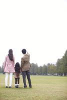 公園で手を繋いで微笑む家族の後ろ姿