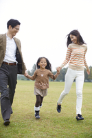 公園で手を繋いで駆ける家族