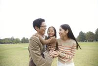 公園で娘を間に笑い合う家族