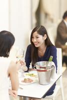 レストランでワインを手に語らう女性二人