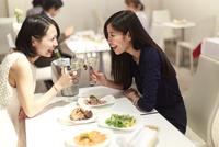 レストランでワインを手に笑い合う女性二人