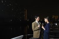 夜景をバックにワインを手に微笑むカップル