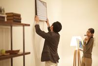 壁に写真を飾る男性とそれを見る女性