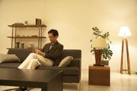 ソファーでスマートデバイスを操作する男性