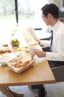 出勤前に新聞を手に朝食をとる男性