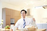 出勤前の朝食中に顔をあげて微笑む男性