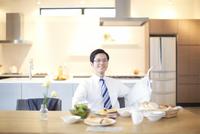 出勤前の朝食中に顔をあげて微笑む男性のスナップ