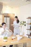 出勤前の朝食を運ぶ奥さんと新聞をたたむ夫