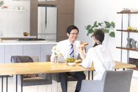 出勤前の朝食で会話する夫婦