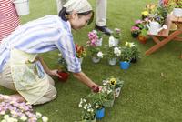 庭に花を飾る奥さん 33000000315| 写真素材・ストックフォト・画像・イラスト素材|アマナイメージズ