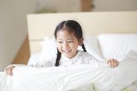 ベットの上で笑うパジャマ姿の女の子