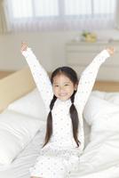 ベットの上で伸びをするパジャマ姿の女の子