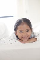 うつ伏せで微笑むパジャマ姿の女の子のスナップ