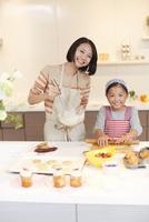 お菓子作りをする母と娘のスナップ