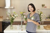 キッチンで花を持って微笑む女性のスナップ