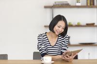 テーブルでスマートデバイス見る女性
