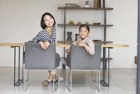 テーブルを背に振り返る母と娘のスナップ 33000000409| 写真素材・ストックフォト・画像・イラスト素材|アマナイメージズ