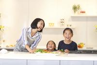 キッチンで料理を前に笑う親子