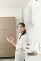 キッチンでスマートホンを持って微笑む主婦のスナップ