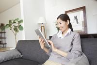 ソファーでスマートデバイスを見て微笑む女性