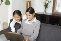 ソファーでノートパソコンを見る母と子