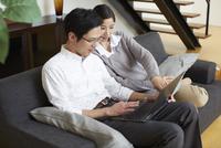 ソファーでノートパソコンを見る夫婦