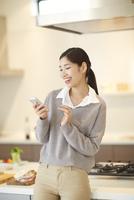 キッチンでスマートフォンを見ながら笑う女性