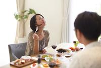 食事中に上を向いて微笑む女性